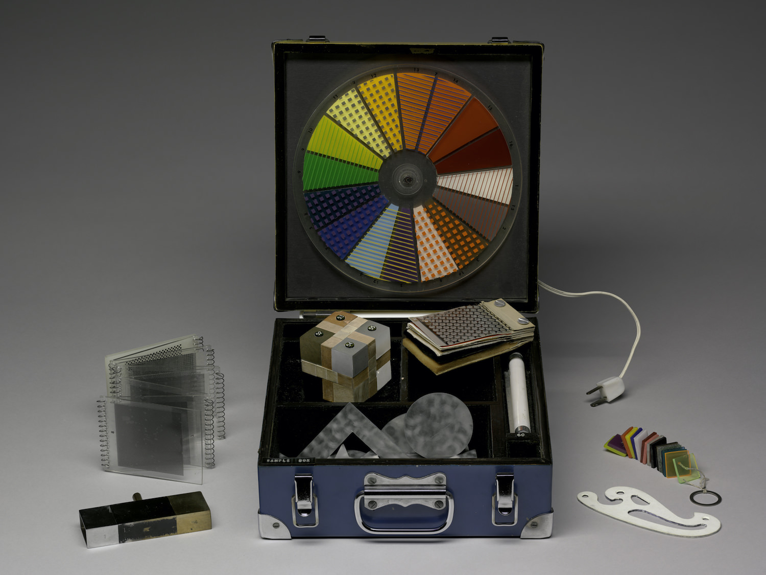 1965, box with mounted Plexiglas wheel and various sample materials, box closed: 11.1 x. 25.4 x 27 cm. Harvard Art Museums/Fogg Museum, Gift of The Collection of John and Kimiko Powers, 1977.16.1