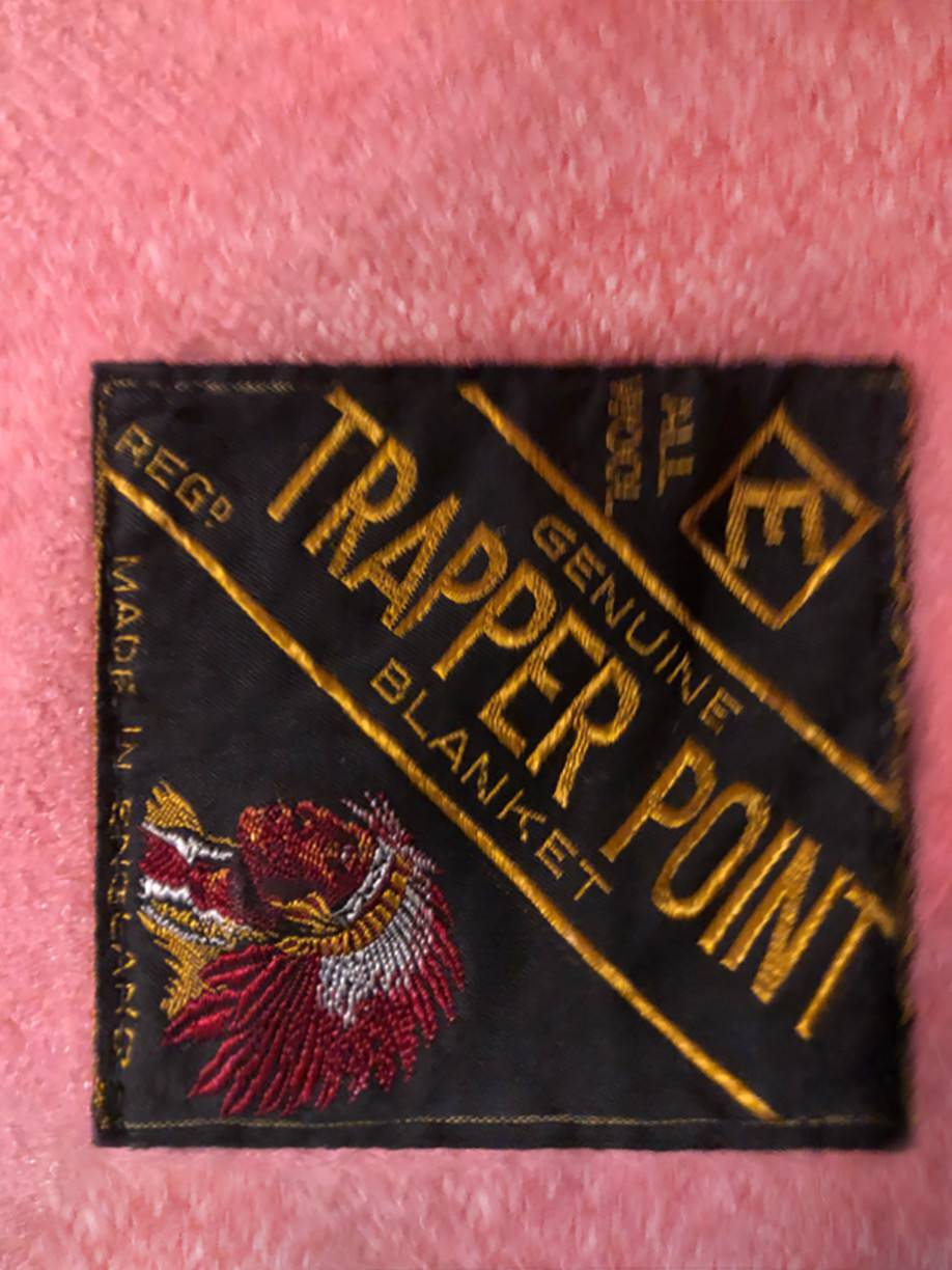 "detail showing the original brand label stitched into the corner of the blanket, ca. 1948. The label authenticates the ""genuine"" Trapper Point blanket by marketing the blanket with a racist stereotype of the ""Indian Chief"". The label also indicates that in spite of a market in the colonies, the blanket is ""Made in England"". Collection of Marlene Kadar."