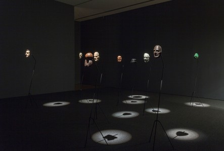 2010–11. 16 mm film transferred to digital (25 minutes, 45 seconds), wooden masks, cast bronze masks, bowler hat, metals stands, suspended mirror, suspended screen, HD projector, media player, and speakers. Dimensions variable