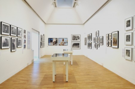 Interior of gallery with works hung on walls and displayed in vitrines