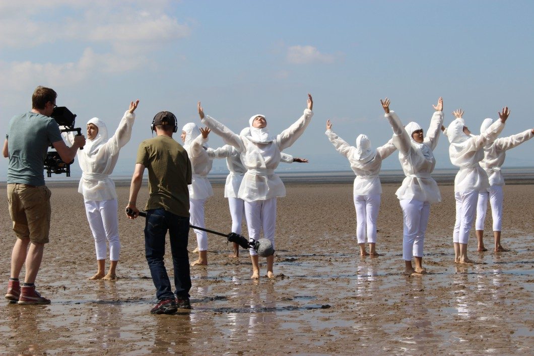 2018. The six core Nations, joined by students from Bath Spa University, perform their final number on Brean Sands, Somerset. The high tide, which was due in at 5pm, was not the only constraint that affected the day's work. The heat, changing light, loud aeroplanes, and dog walkers all slowed the shoot; but because such elements had been factored into the schedule, filming still finished on time.