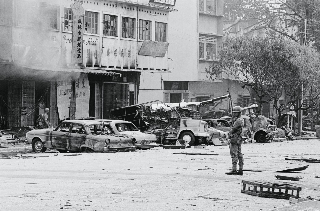 Patrol Streets. Kuala Lumpur, Malaysia: Troops of the Malay Royal Regiment patrol damaged and littered streets of the Chinatown area in Kuala Lumpur