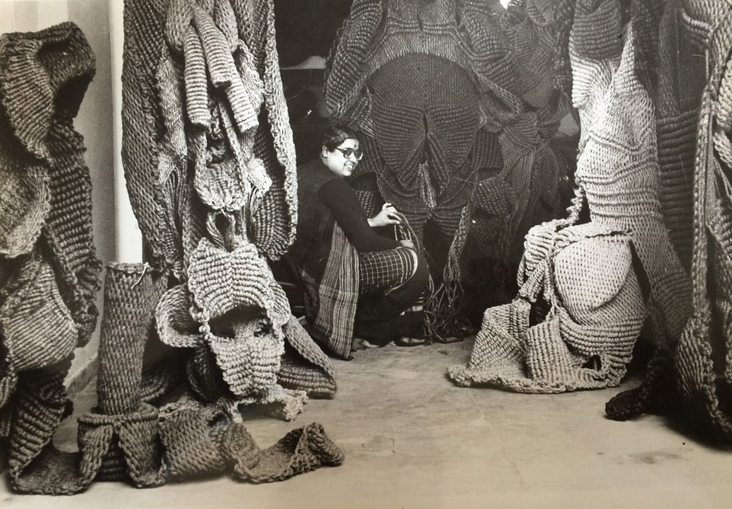 Portrait of artist surrounded by woven sculptures