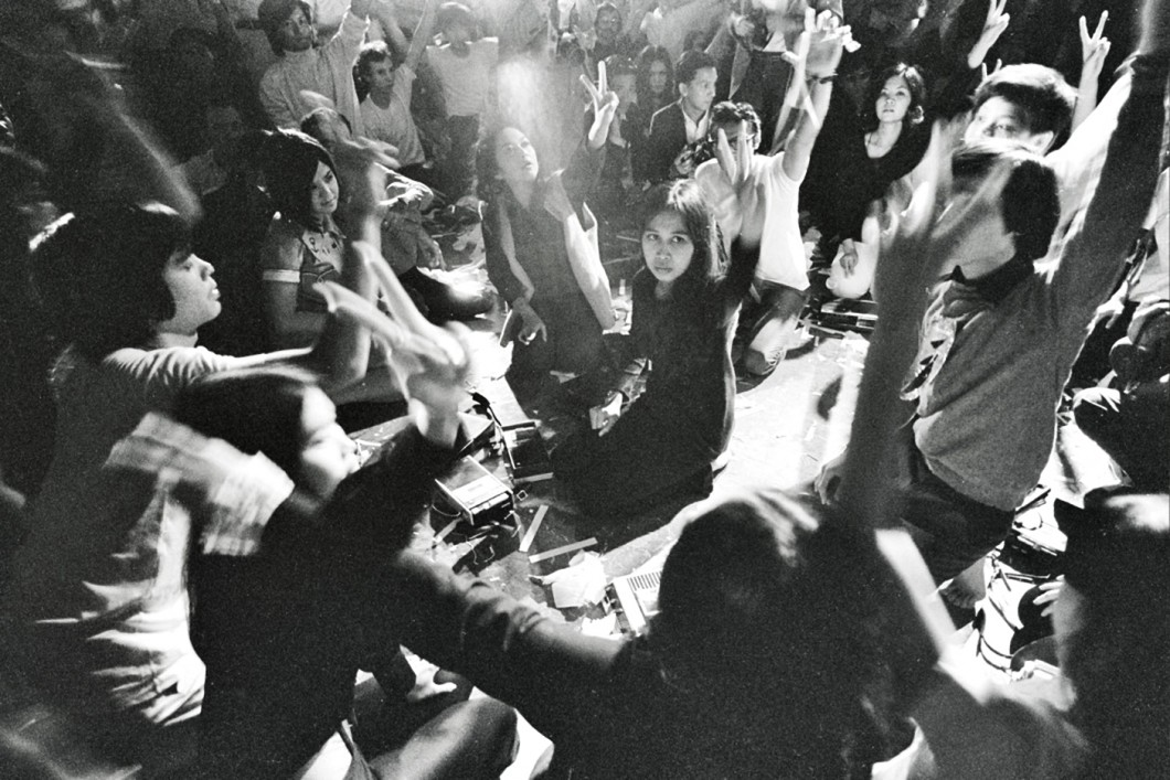 Black and white photograph of crowded kneeling group, each raising a hand gesturing a peace sign