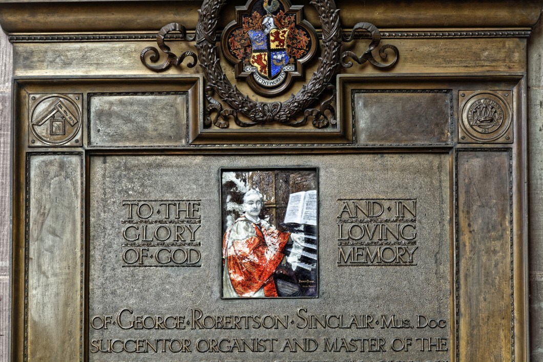 with a relief showing Sinclair at the organ console, signed by Fanny Bunn, at Hereford Cathedral.