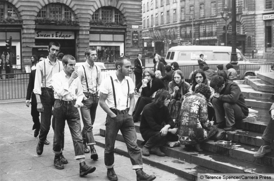 A group of Skinheads walk past a group of hippies sitting on the steps of Eros in Piccadilly Circus